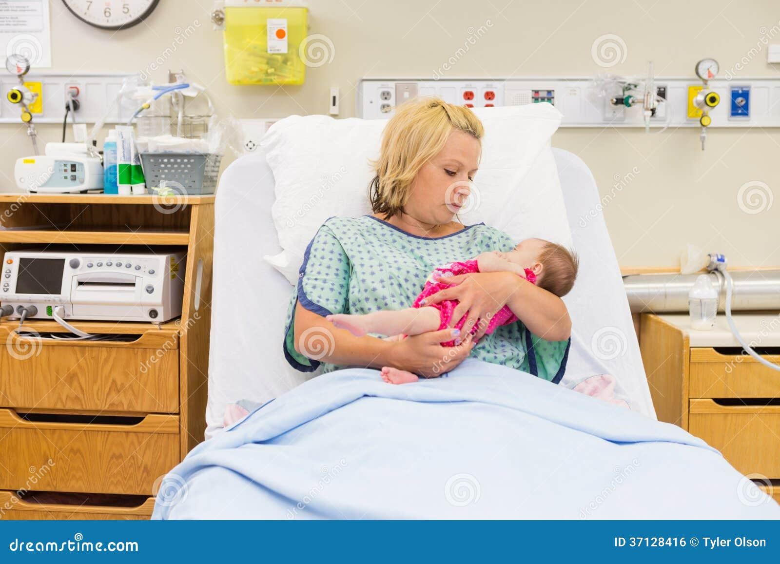 Mãe que olha o bebê recém-nascido ao sentar-se
