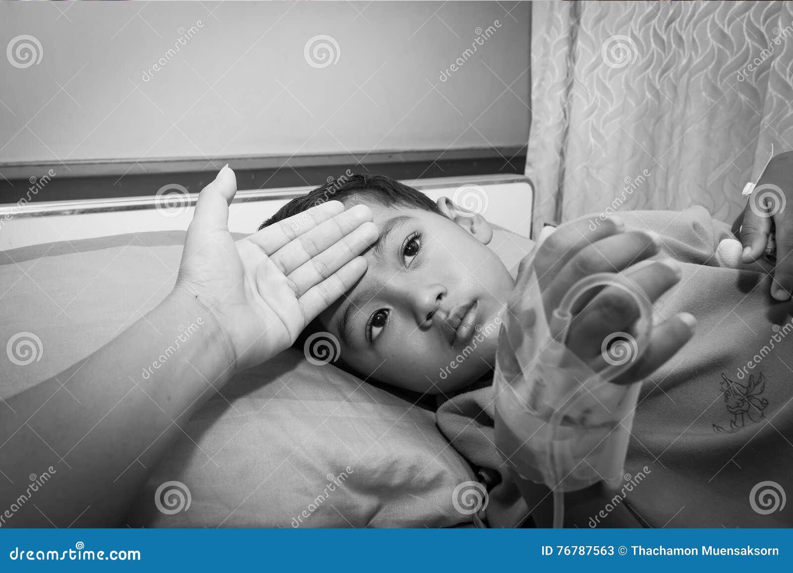 A mãe verificou para ver se há a febre seu doente do filho ao descansar