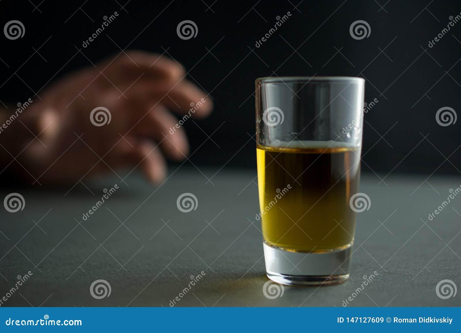 A mão alcança para um vidro da bebida do uísque ou do conhaque ou do álcool