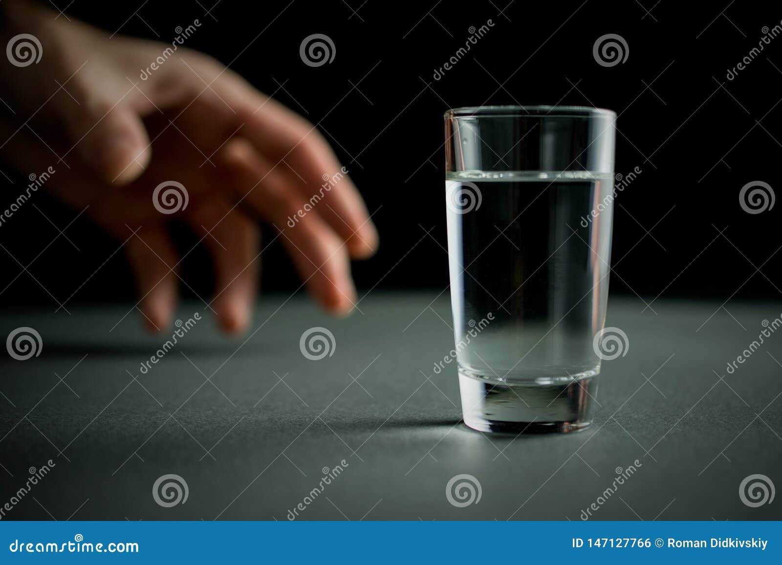 A mão alcança para um vidro da vodca