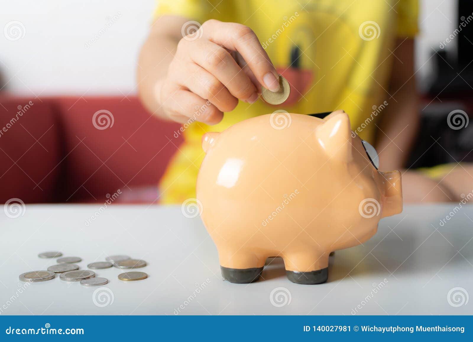 Mão ascendente próxima da mulher que põe moedas no mealheiro