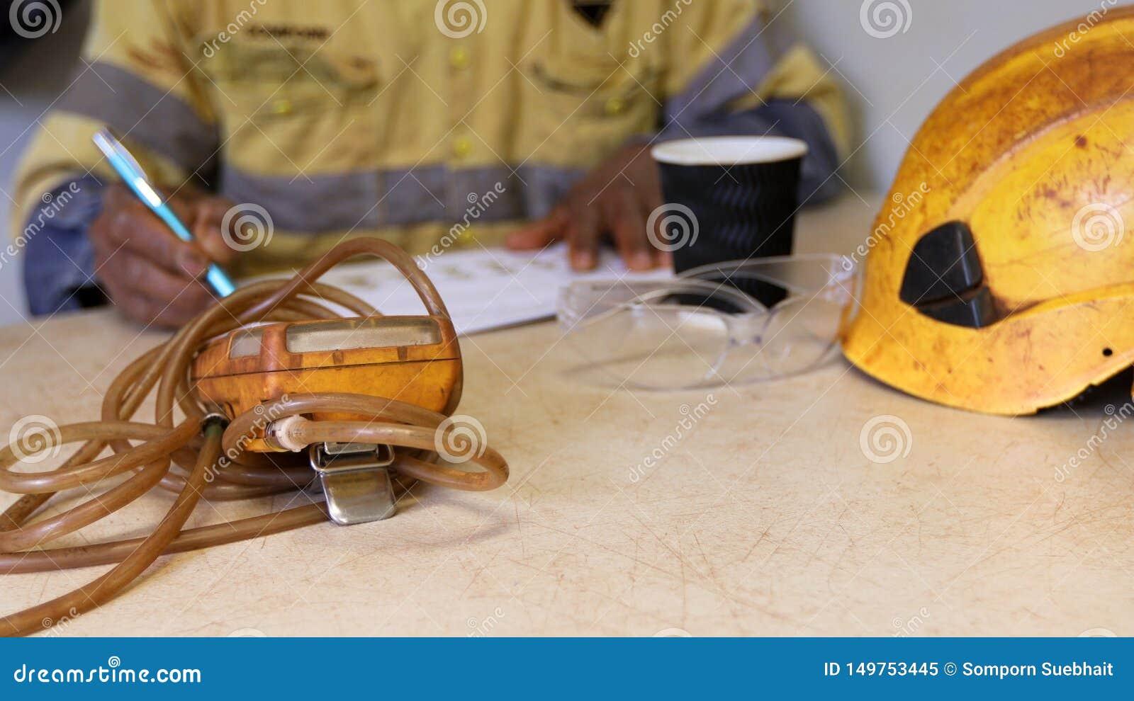 Mão asiática avaliação escrita de JHSrisk da análise de perigo do trabalho na tabela ao trabalhar no espaço restrito limitado com