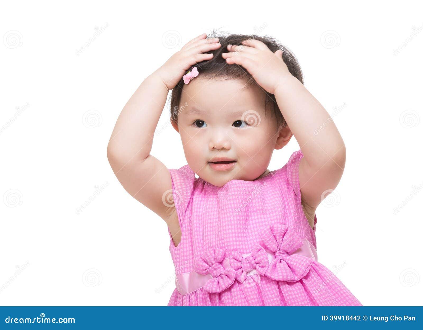 A mão asiática da menina dois toca em seu cabelo