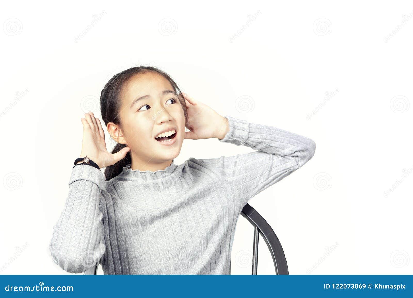 A mão asiática do aumento do adolescente até a audição isolou o backgroun branco