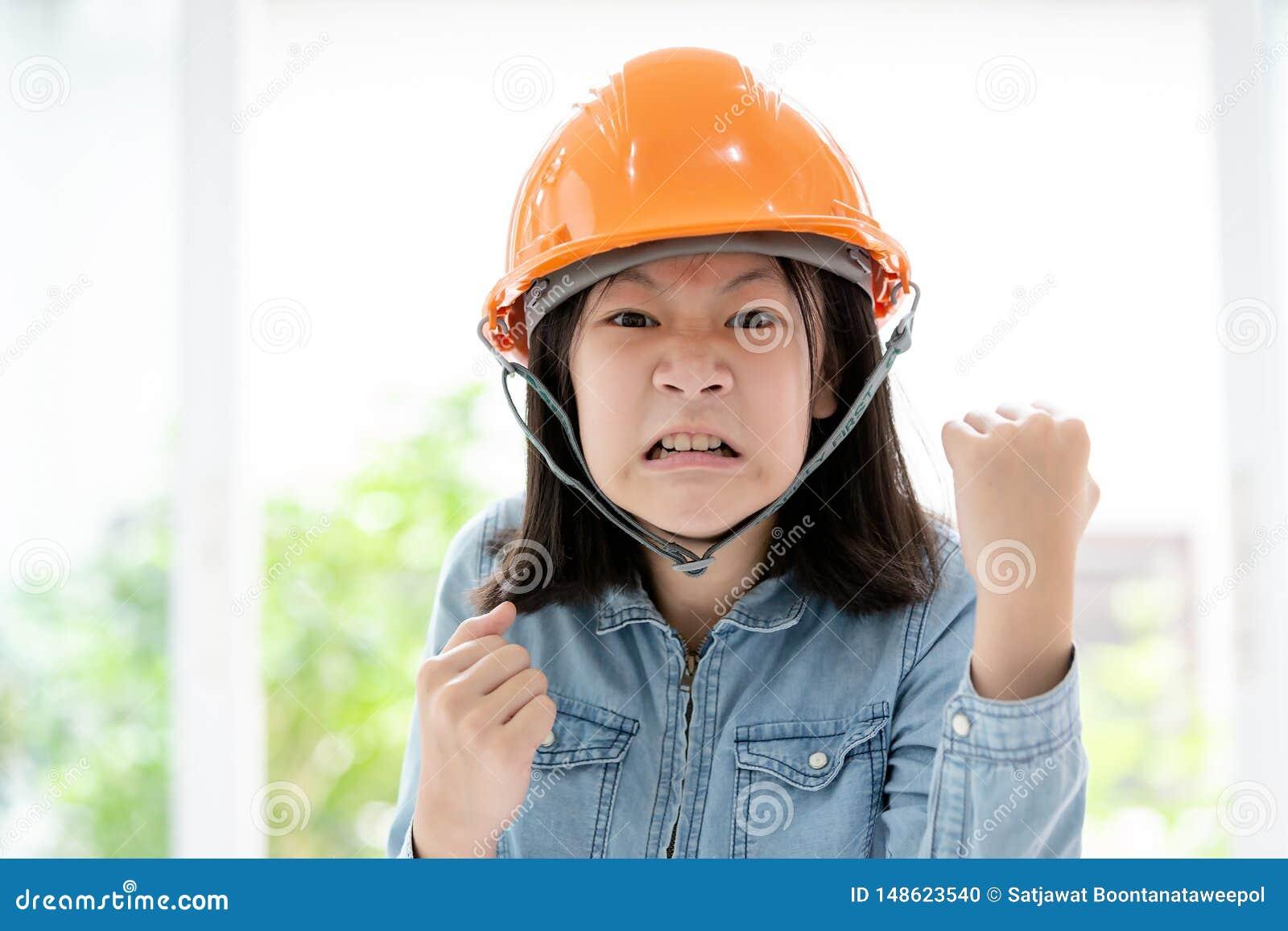 M?o asi?tica irritada da menina com gesto do punho com capacete de seguran?a ou capacete de seguran?a, retrato do close up do pun