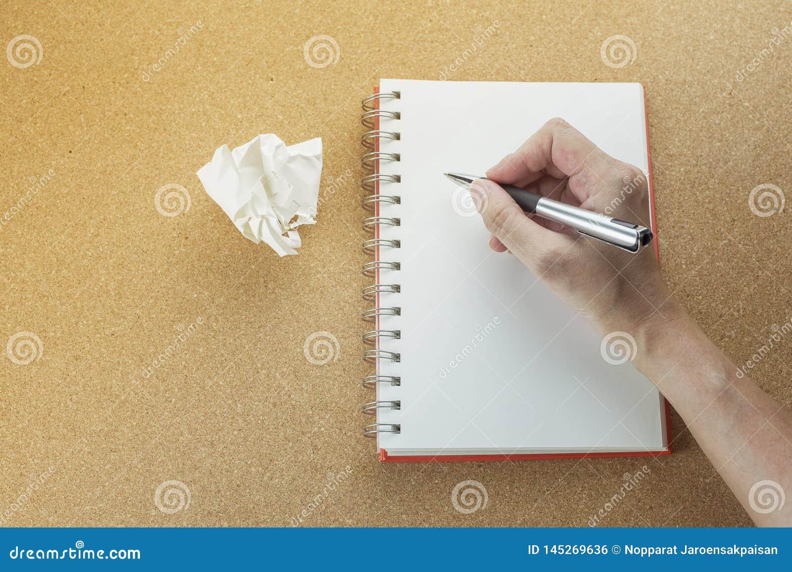 Mão com escrita da pena no caderno espiral vazio