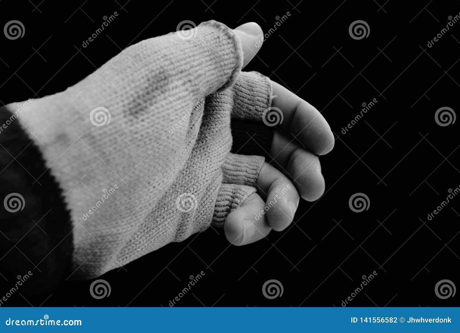 A mão com luva velha que falta o dedo cobre em um fundo preto e em preto e branco
