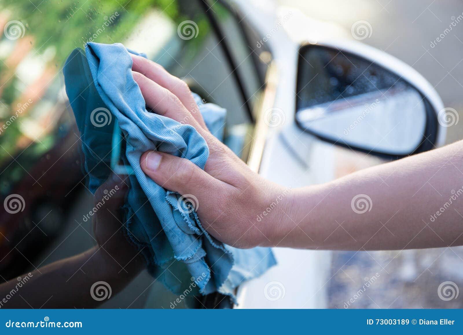 Mão com o carro da limpeza de pano do microfiber
