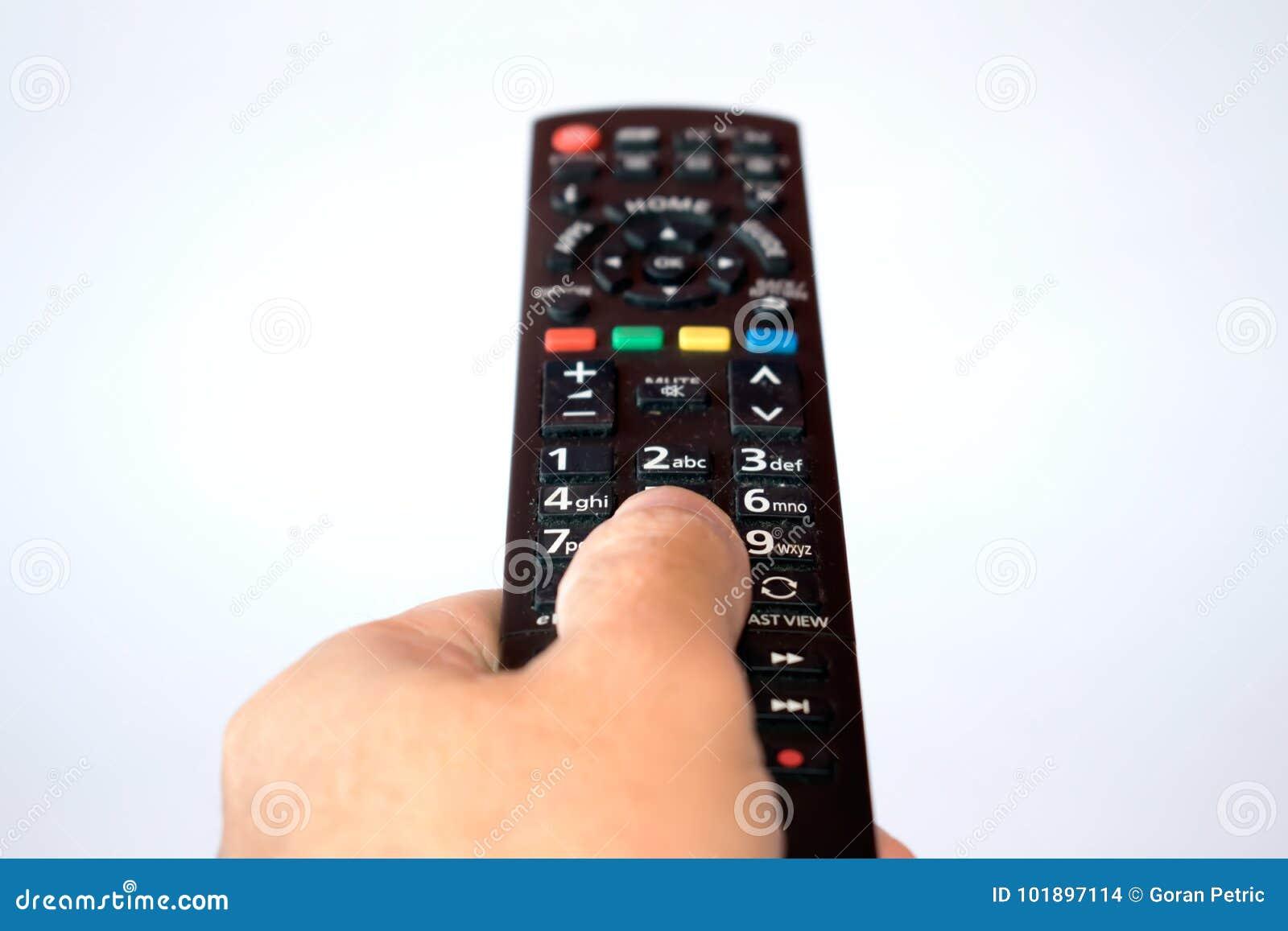 Mão com o controlo a distância da tevê isolado no fundo branco