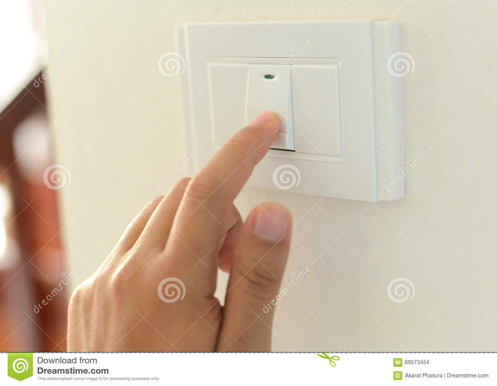 Mão com o dedo no interruptor da luz,