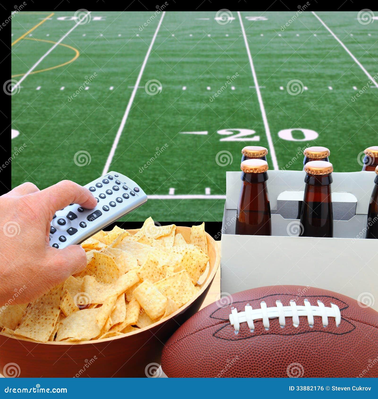 Mão com telecontrole, cerveja, microplaquetas e futebol da tevê