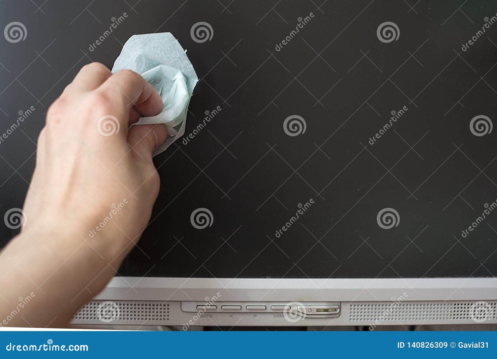 A mão com um pano úmido para monitores do LCD limpa o monitor