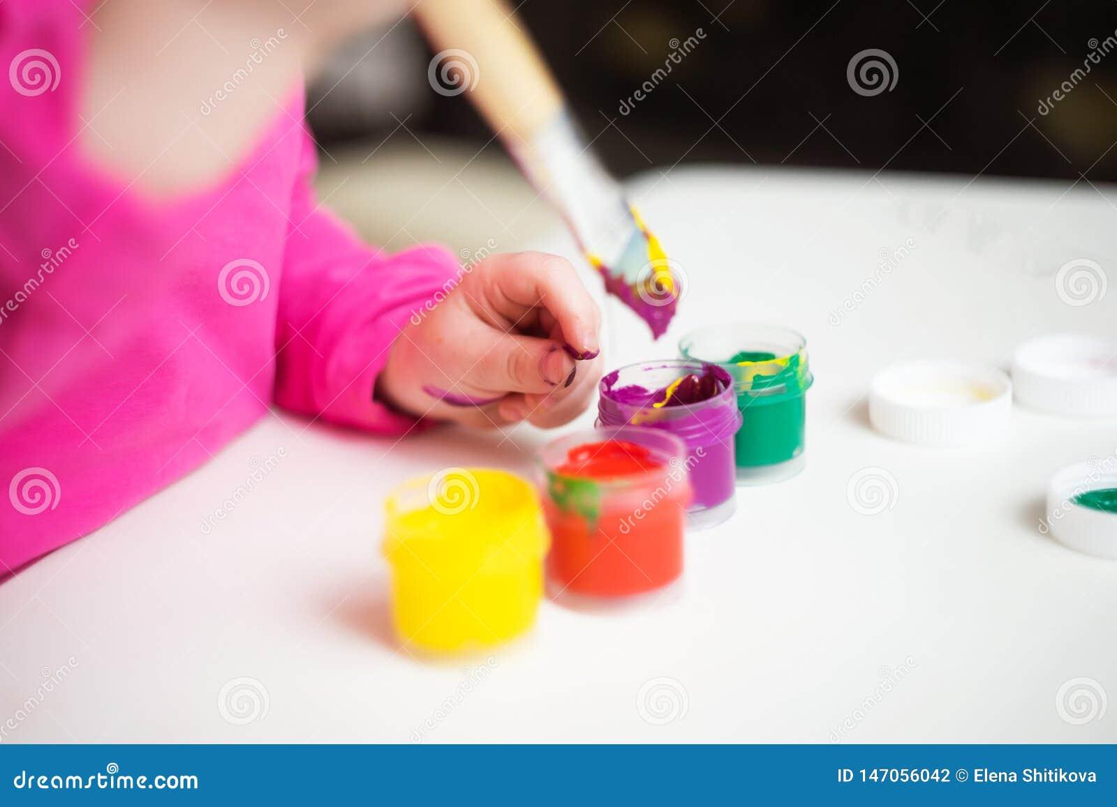 A mão da criança guarda a escova de pintura