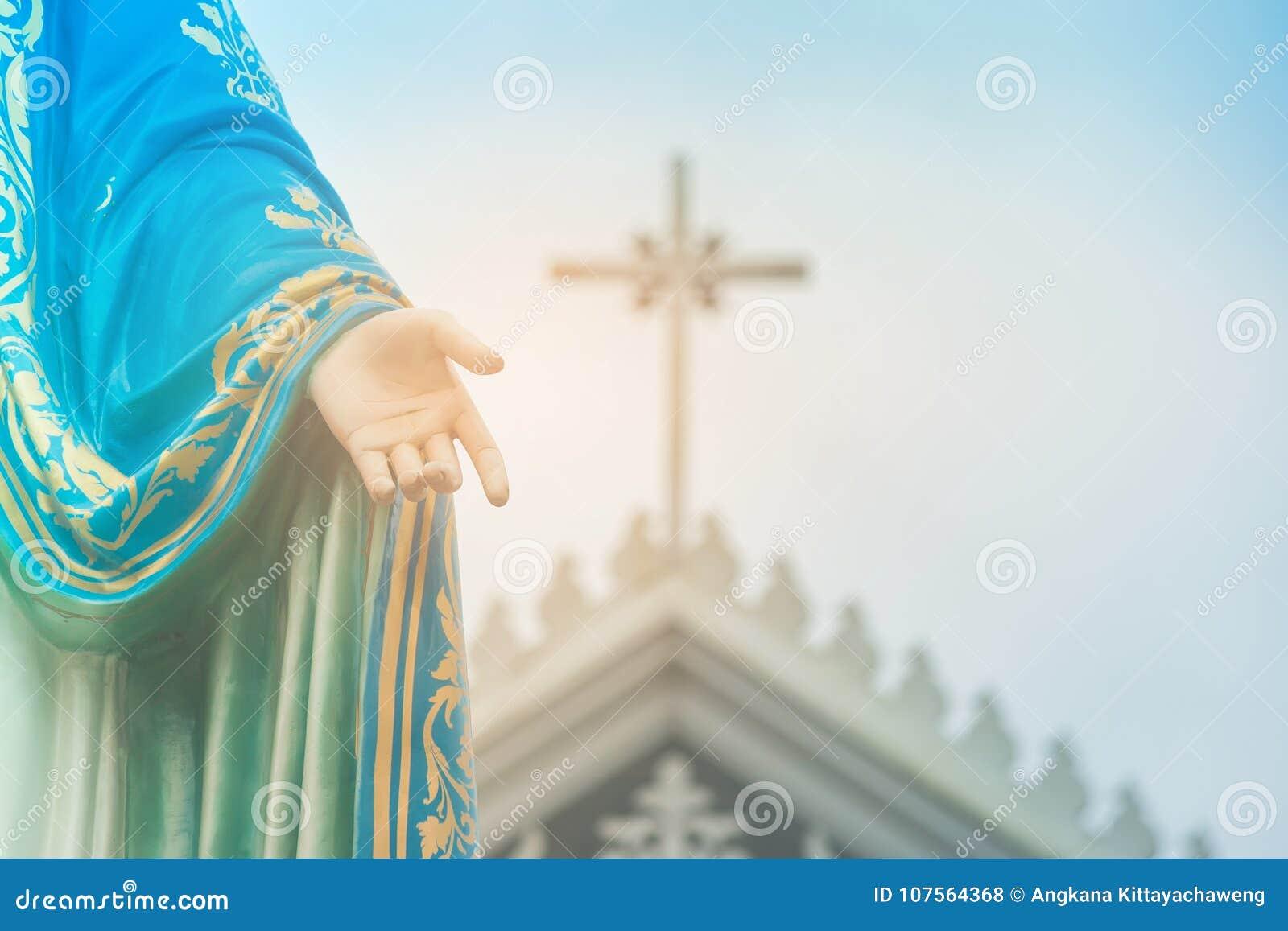 Mão da estátua abençoada da Virgem Maria que está na frente de Roman Catholic Diocese com crucifixo ou cruz
