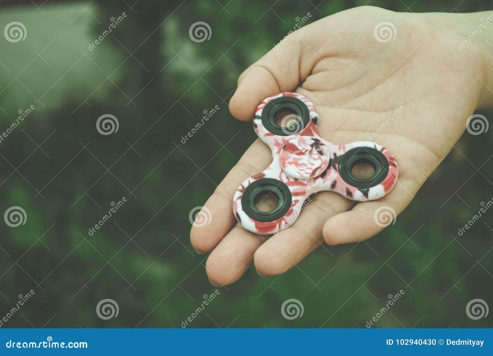 A mão da menina guarda e mostra o brinquedo do girador da inquietação da mão