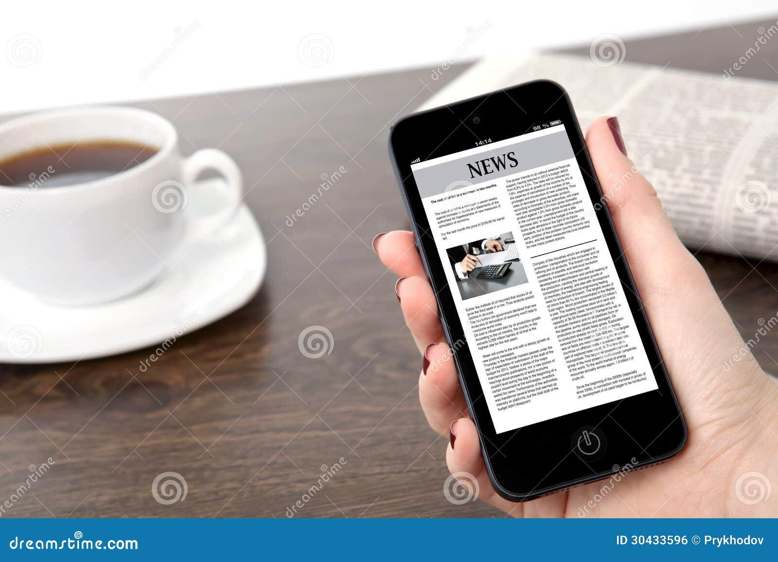 Mão da mulher de negócios que mantem um telefone com notícias de negócios contra o th