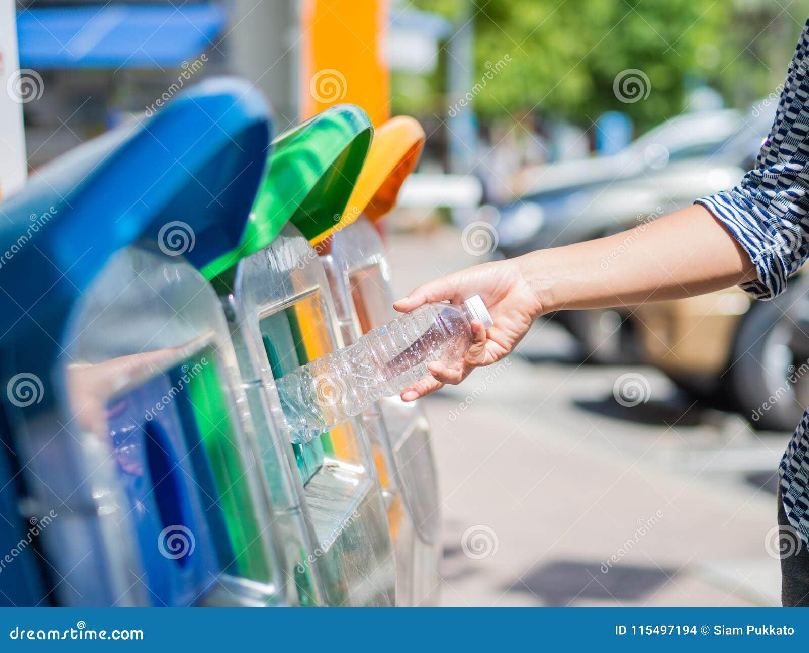 Mão da mulher do retrato do close up que joga a garrafa de água plástica vazia no escaninho de reciclagem