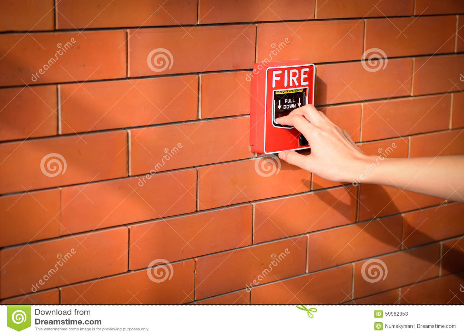 A mão da mulher está puxando o alarme de incêndio na parede de tijolo