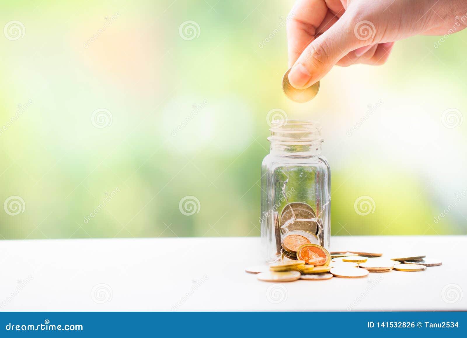 A mão da mulher pôs a moeda em um frasco economia do dinheiro Conceito do investimento