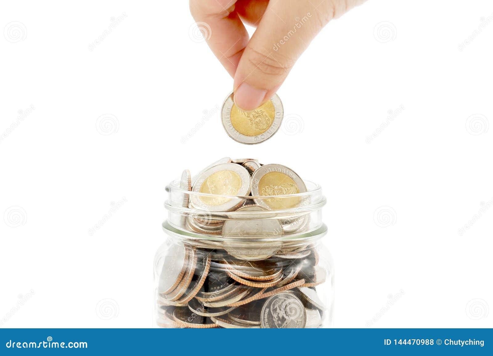 A mão da mulher que deixa cair a moeda nova do baht dez tailandês em um frasco de vidro completamente das moedas