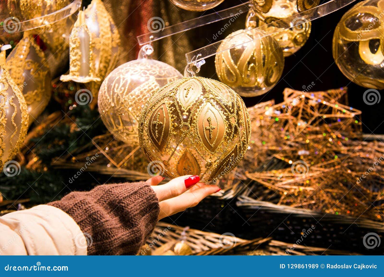 Mão da mulher que guarda a bola belamente crafted da decoração do Natal na cor do ouro com projeto decorativo