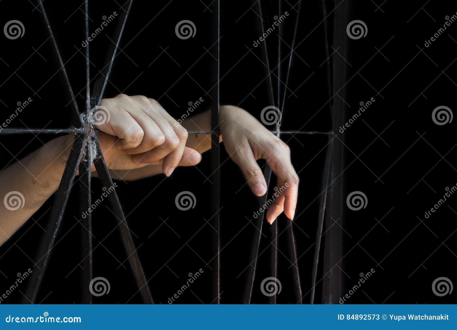 Mão da mulher que guarda a gaiola, abuso, conceito de tráfico humano