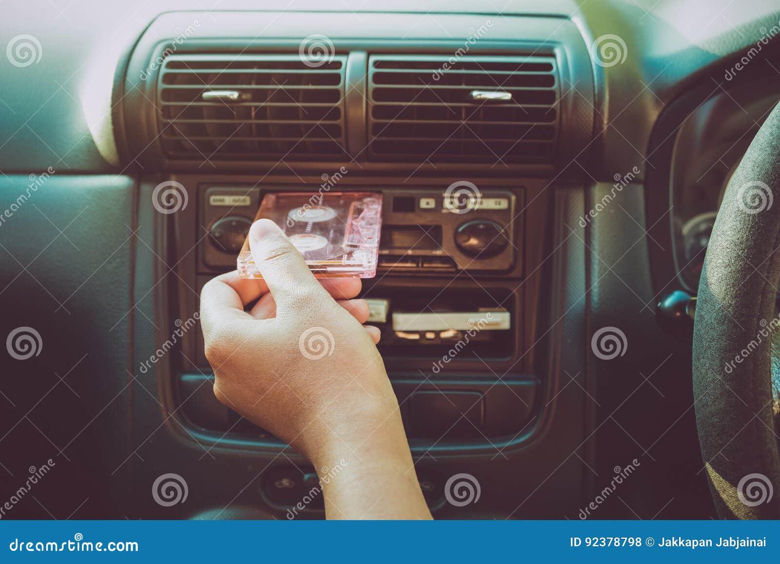 A mão da mulher que guarda a gaveta de fita no carro para conduzir escuta música