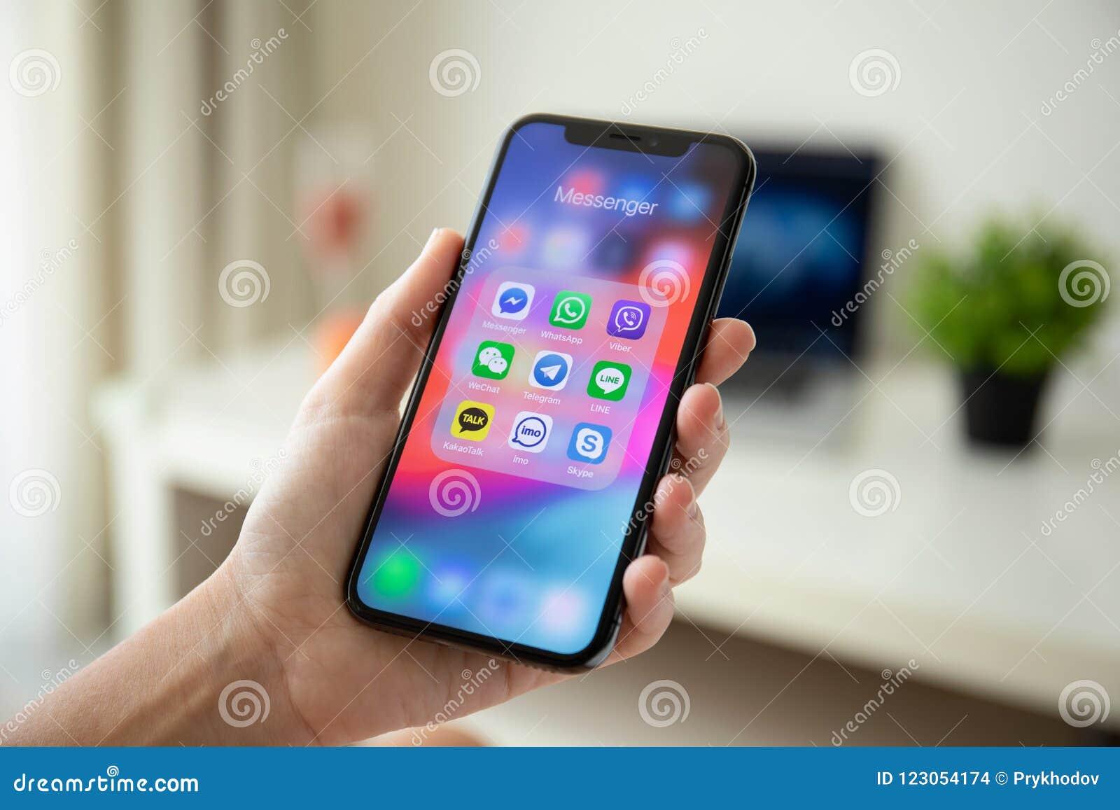 Mão da mulher que guarda o iPhone X com o mensageiro social dos trabalhos em rede