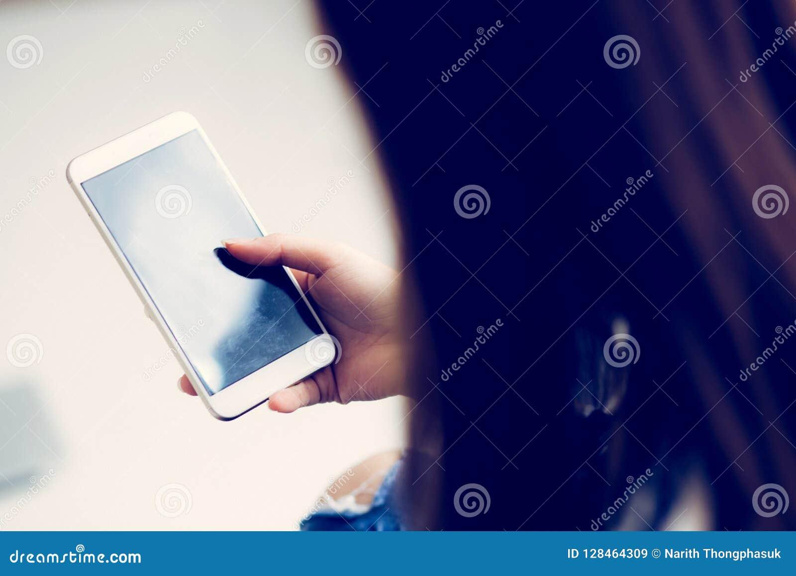 Mão da mulher que guarda o telefone celular esperto com mensagem ou email, gir