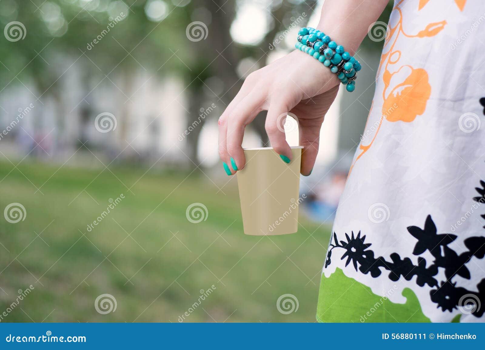 A mão da mulher que guarda a xícara de café