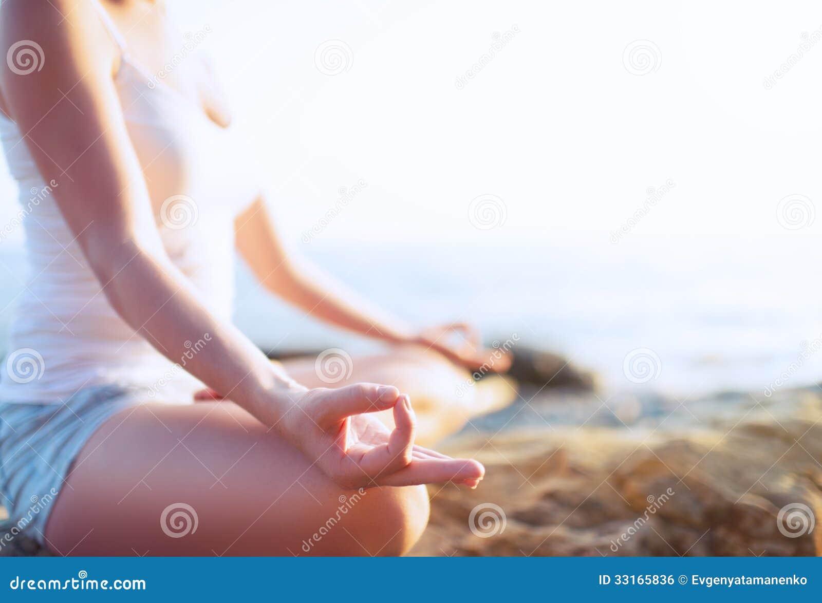 Mão da mulher que medita em uma pose da ioga na praia