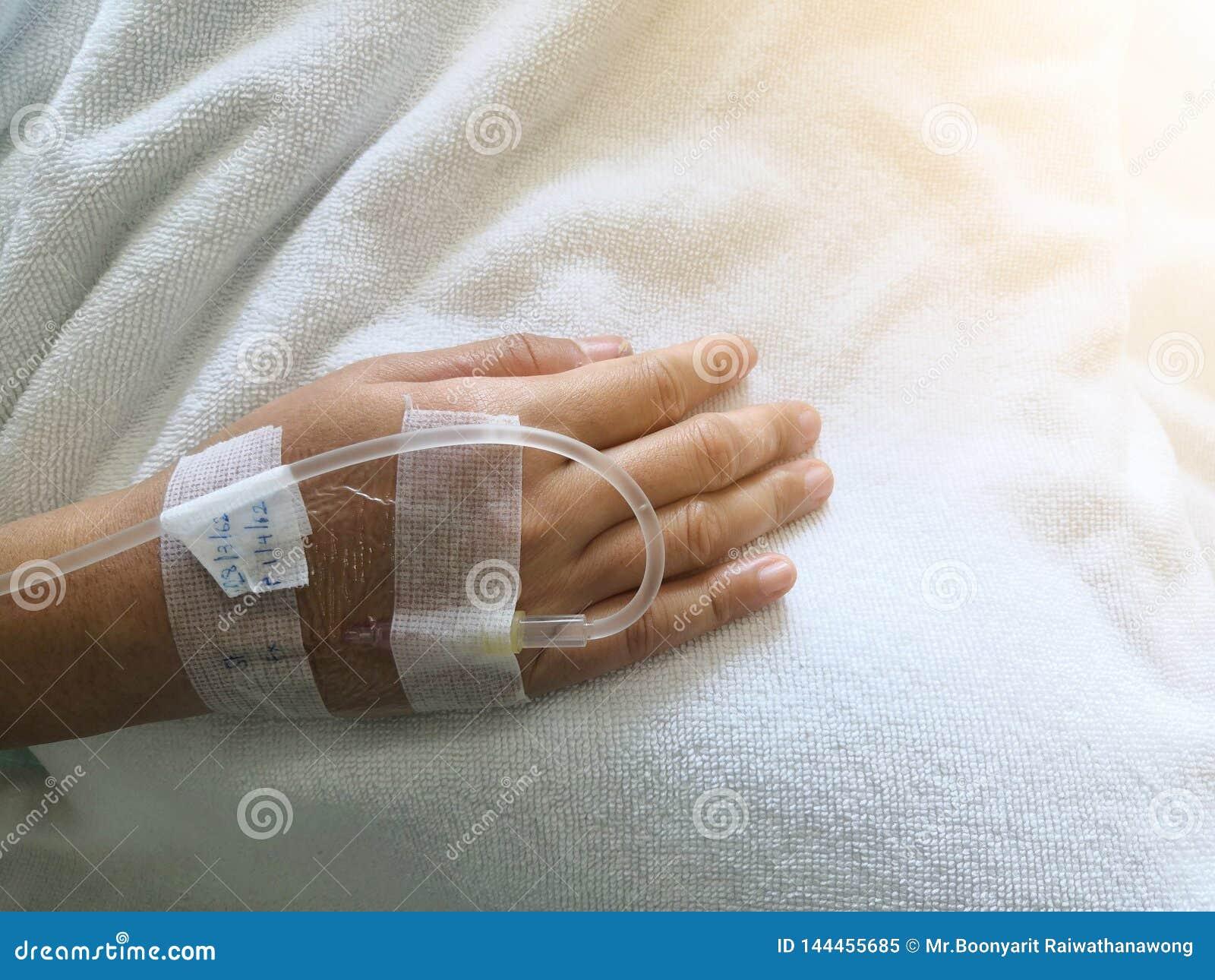 A mão da mulher, solução para intravenoso, a salmoura do cloreto de sódio, tratamento médico, intravenosos salino, hospitais usa