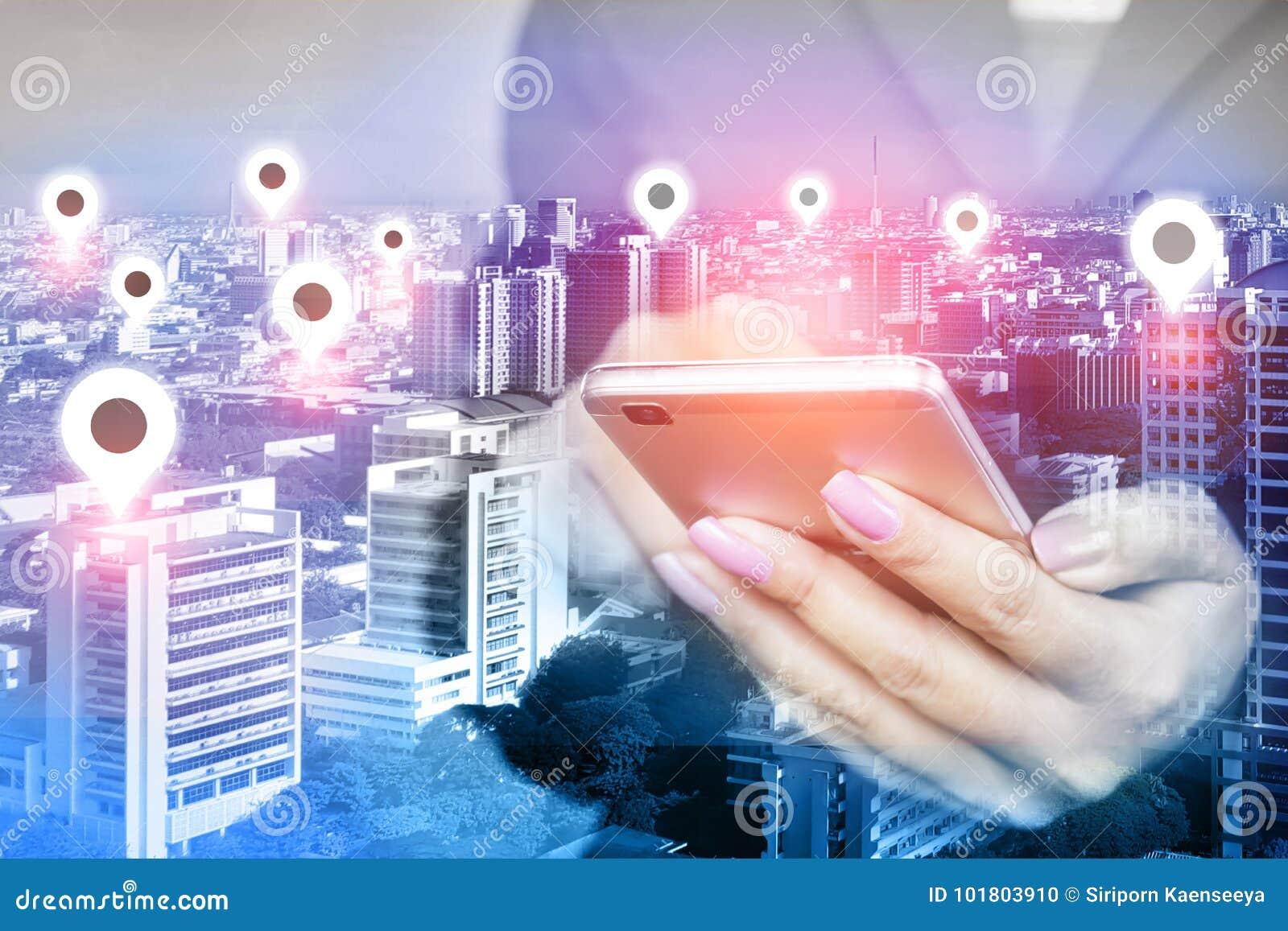 Mão da mulher usando o telefone celular com ícone sobre a cidade esperta, conceito do lugar da conexão de rede