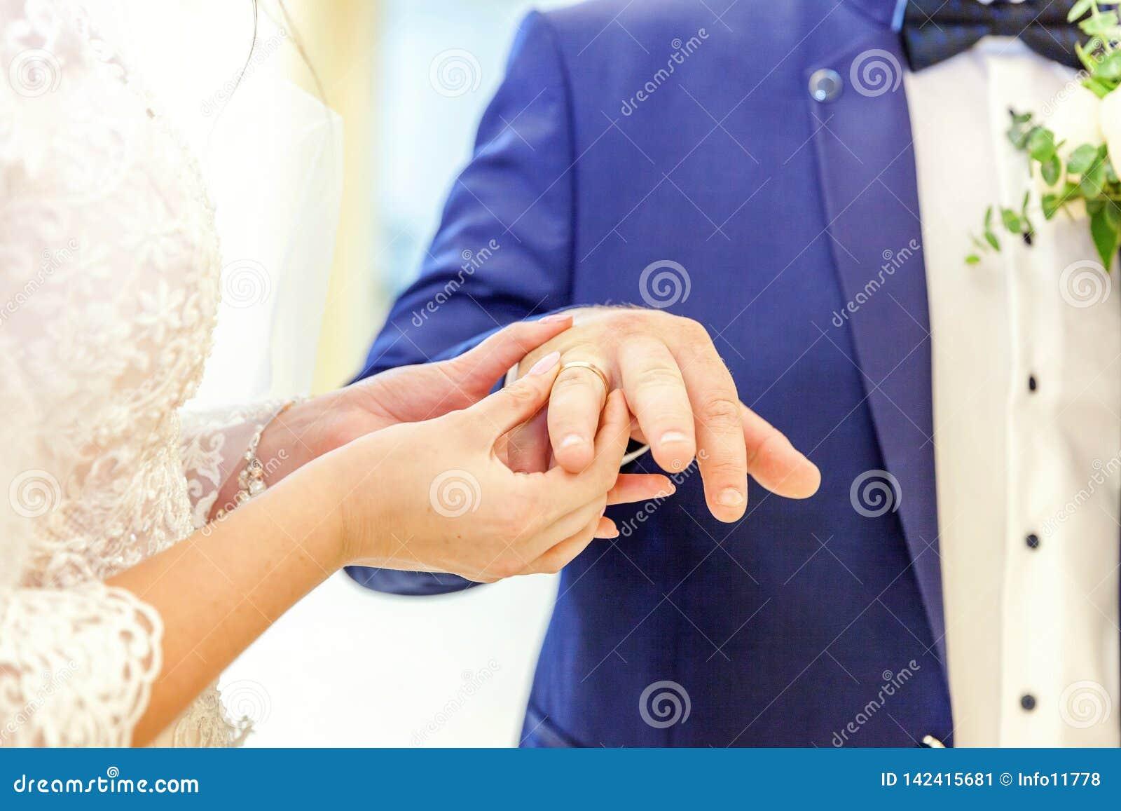 Mão da noiva que põe a aliança de casamento sobre o dedo do noivo