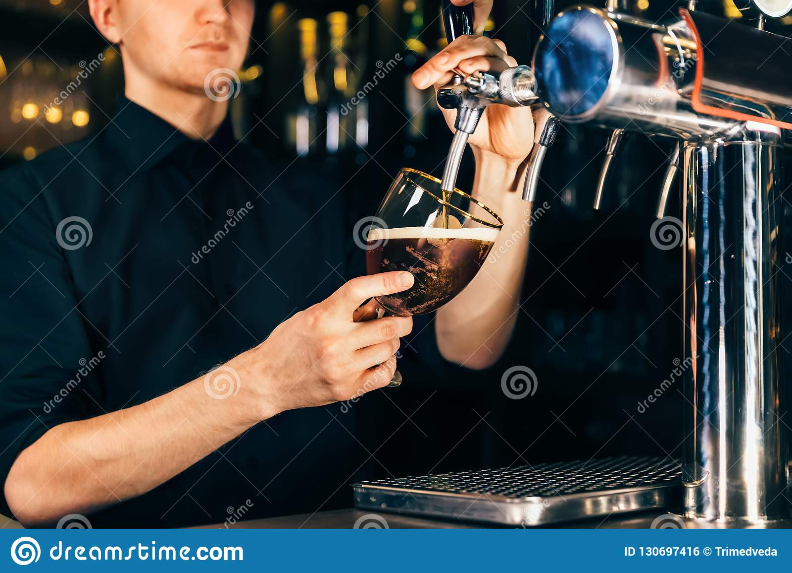 Mão do barman que derrama uma grande cerveja de cerveja pilsen na torneira em um restaurante ou em um bar