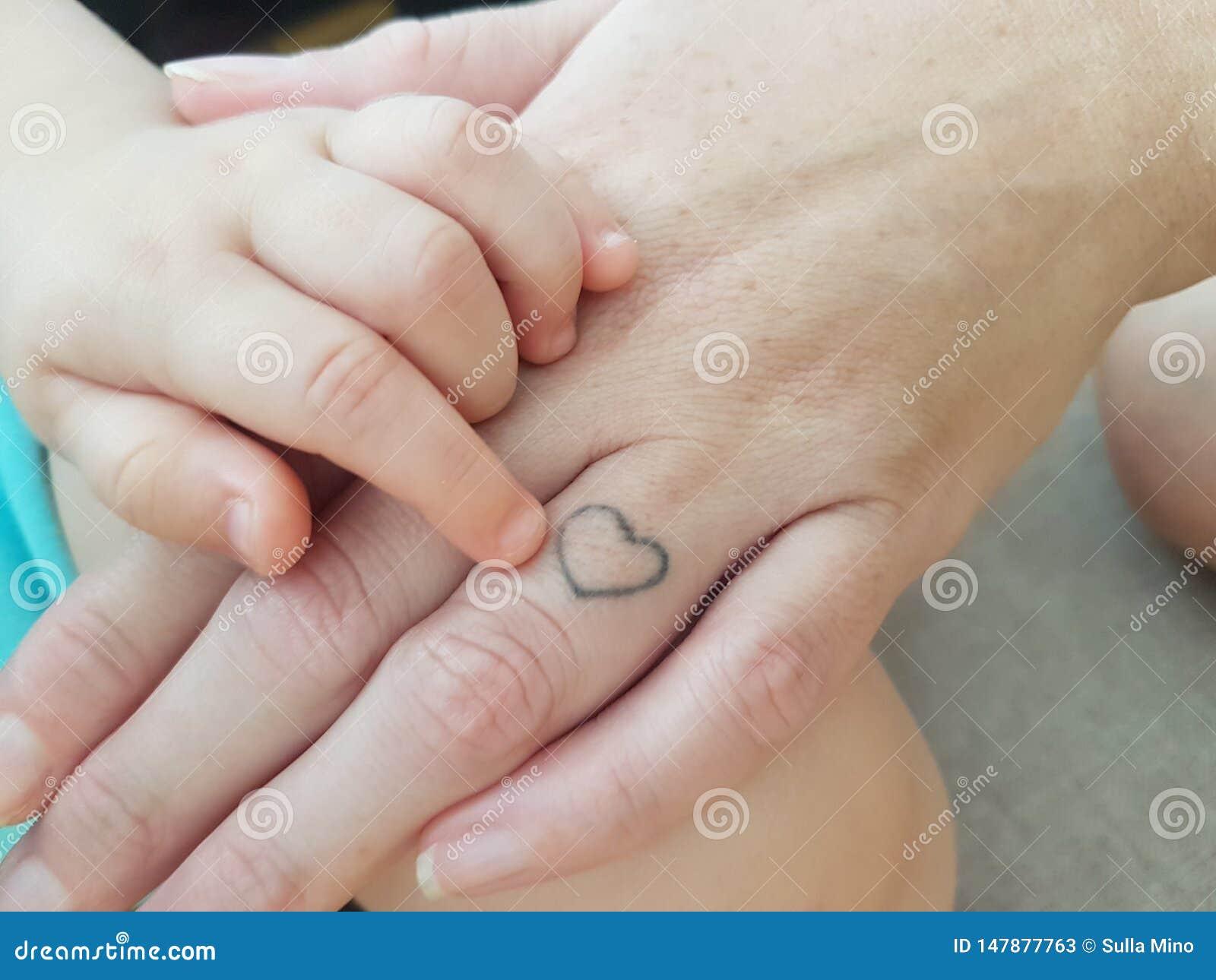 Mão do bebê com mão da mamã