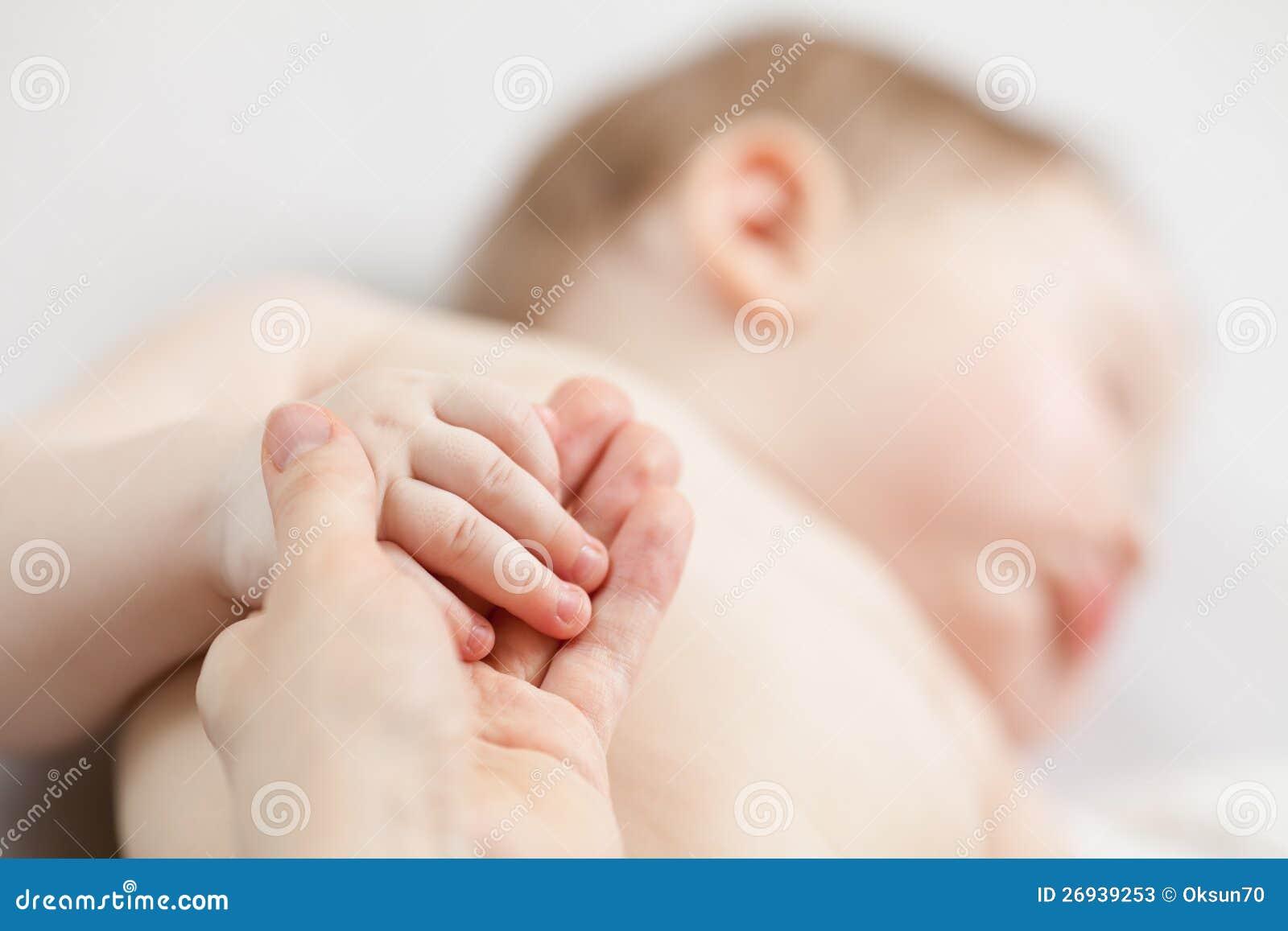 Mão do bebê da terra arrendada da mão da matriz