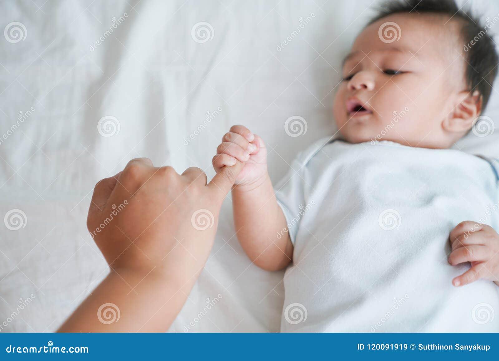 Mão do bebê de sono na mão do fim da mãe acima na cama, na família nova e na proteção do bebê do conceito da mamã