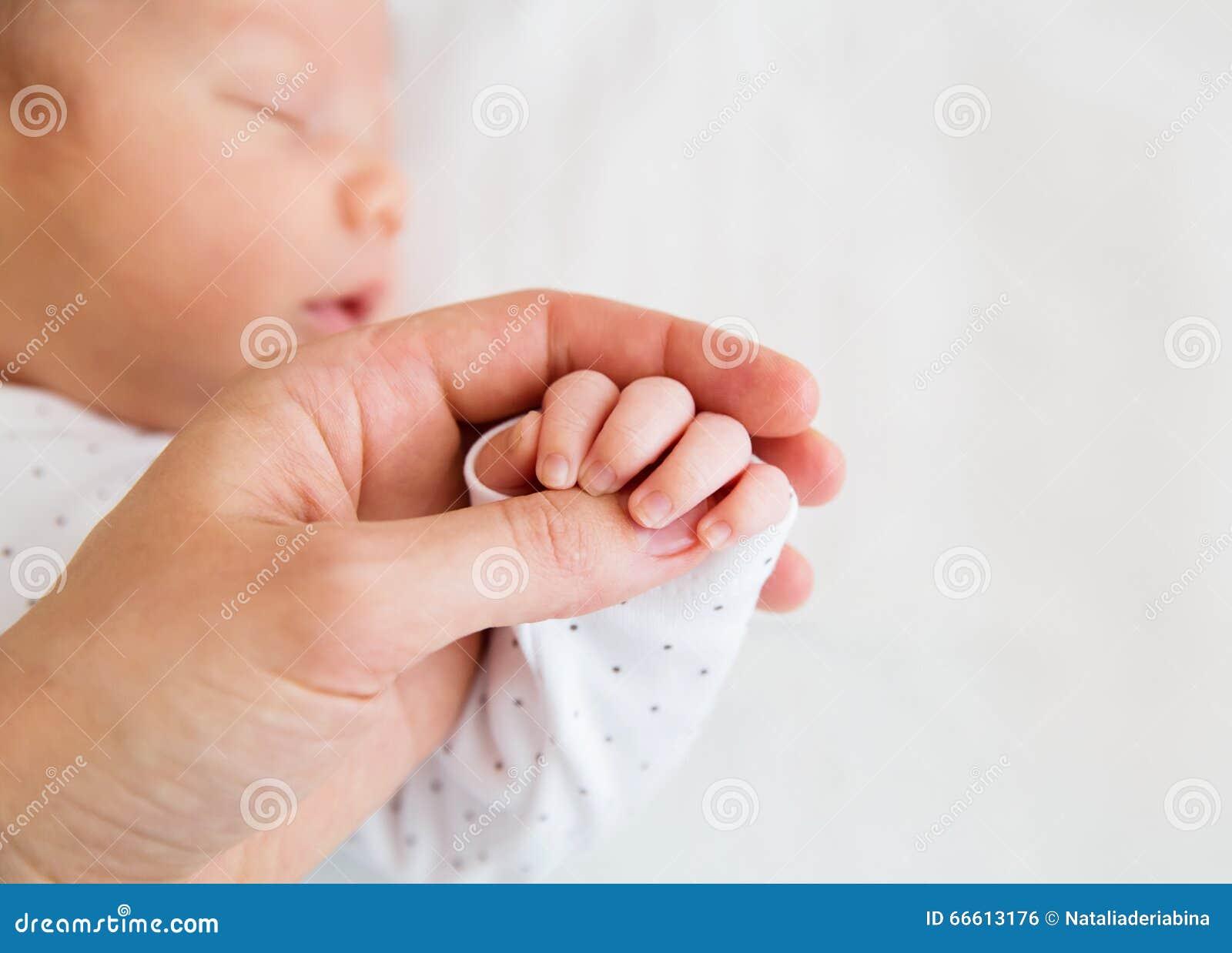 Mão do close-up de um bebê recém-nascido