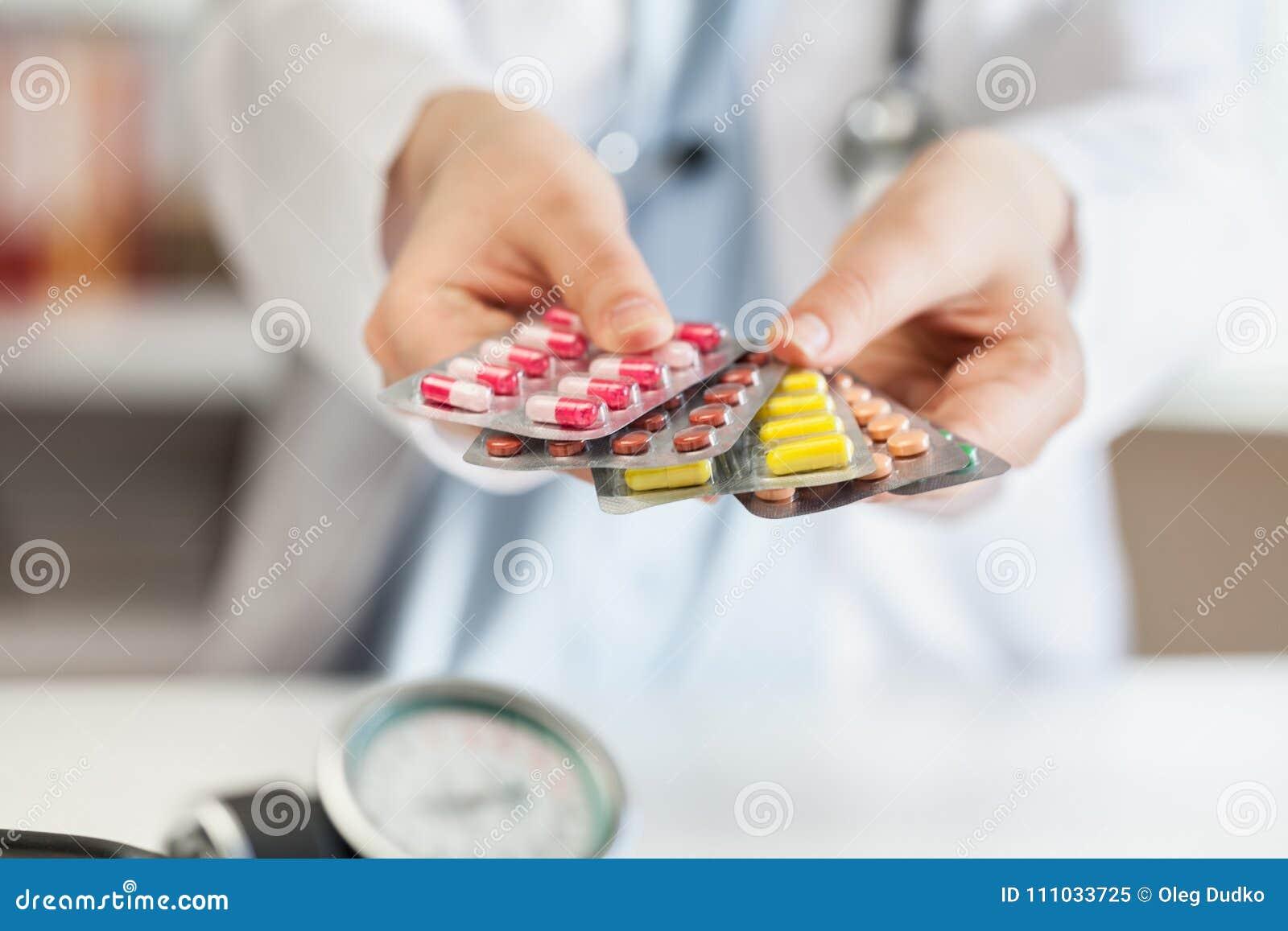 Mão do doutor que guarda o comprimido