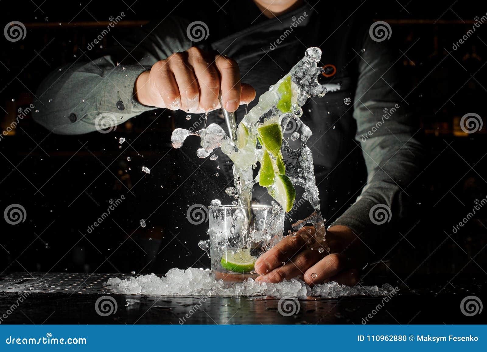 Mão do empregado de bar que espreme o suco fresco do cal que faz o cocktail de Caipirinha