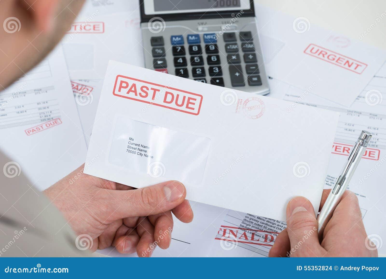 Mão do empresário com envelope passado-devido
