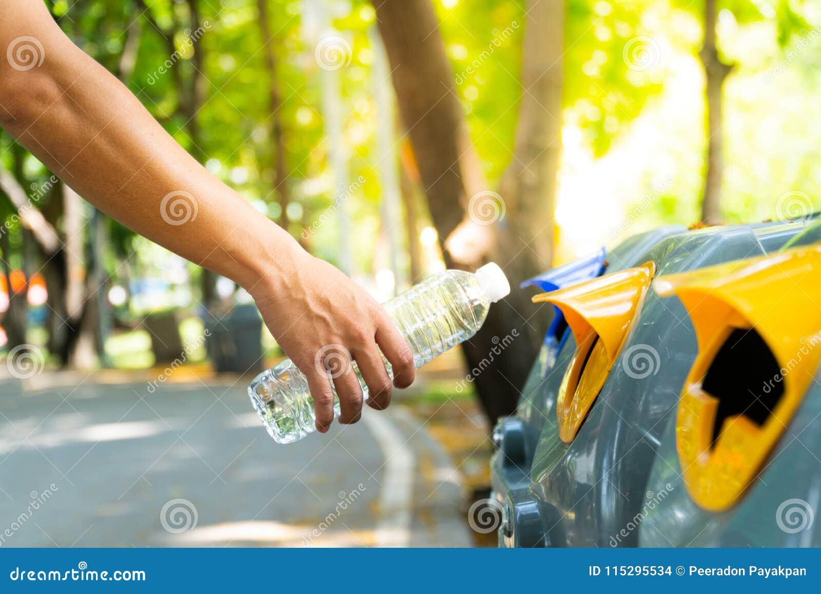 Mão do homem do close up que joga a garrafa de água plástica vazia para no rec