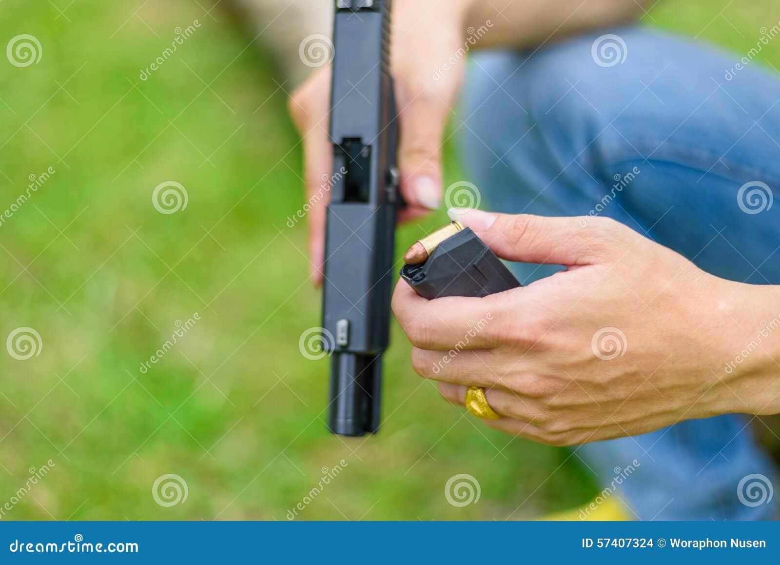 Mão do homem da arma no fundo verde