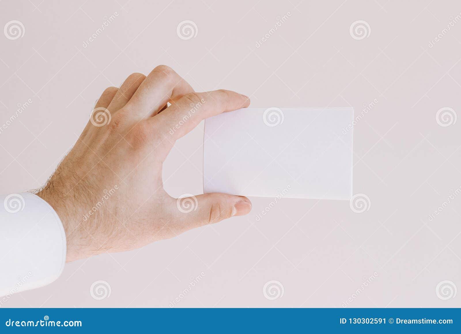 A mão do homem na camisa branca que mostra um cartão vazio