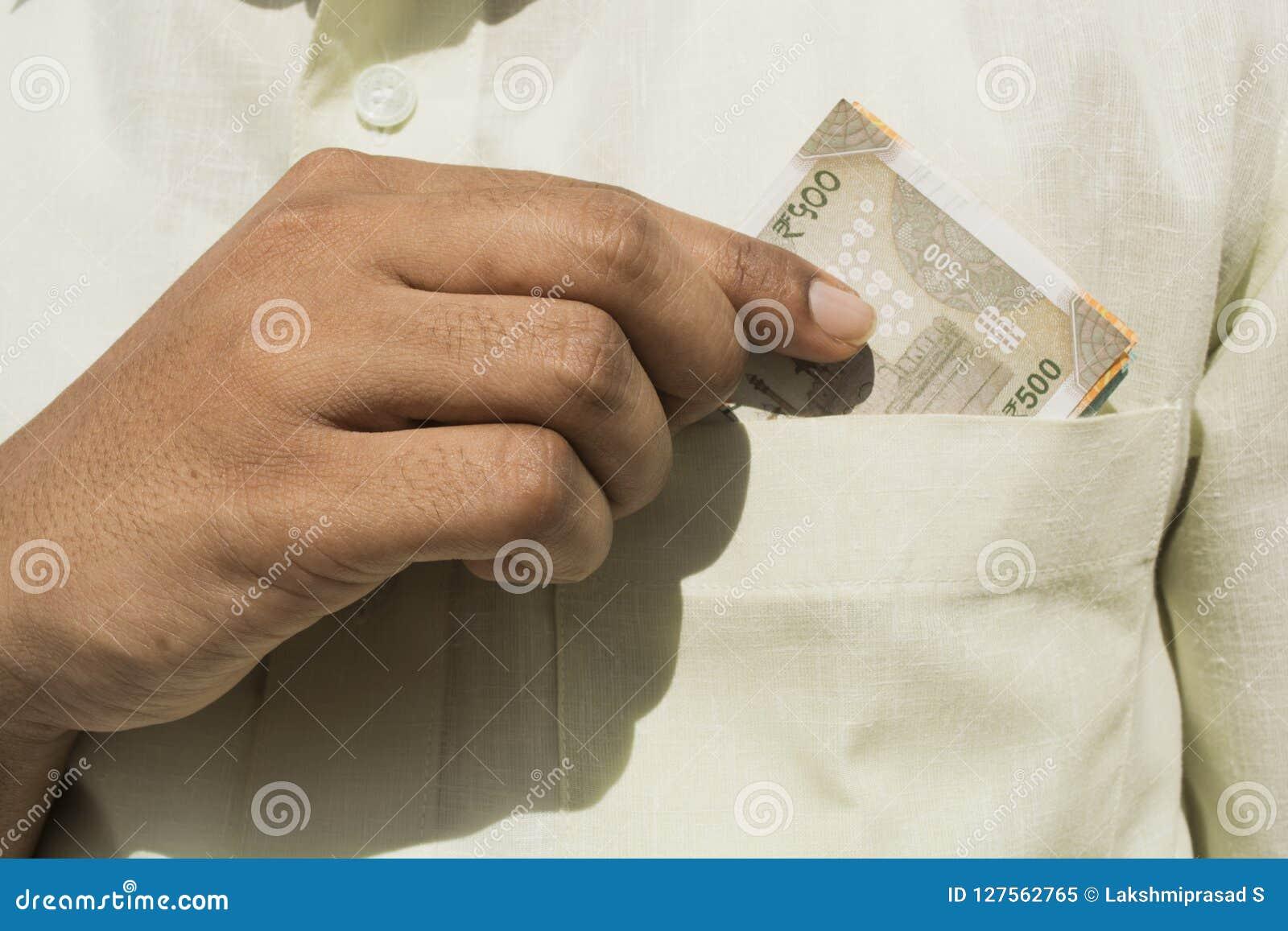 A mão do homem pega uma nota nova da moeda de 500 indianos fora de seu fim do bolso