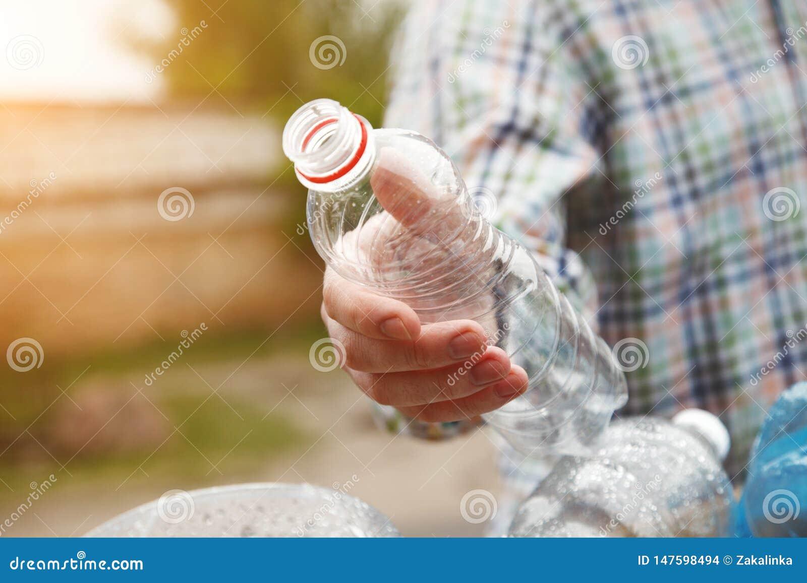 A mão do homem que joga a garrafa plástica reciclável transparente clara no escaninho de lixo