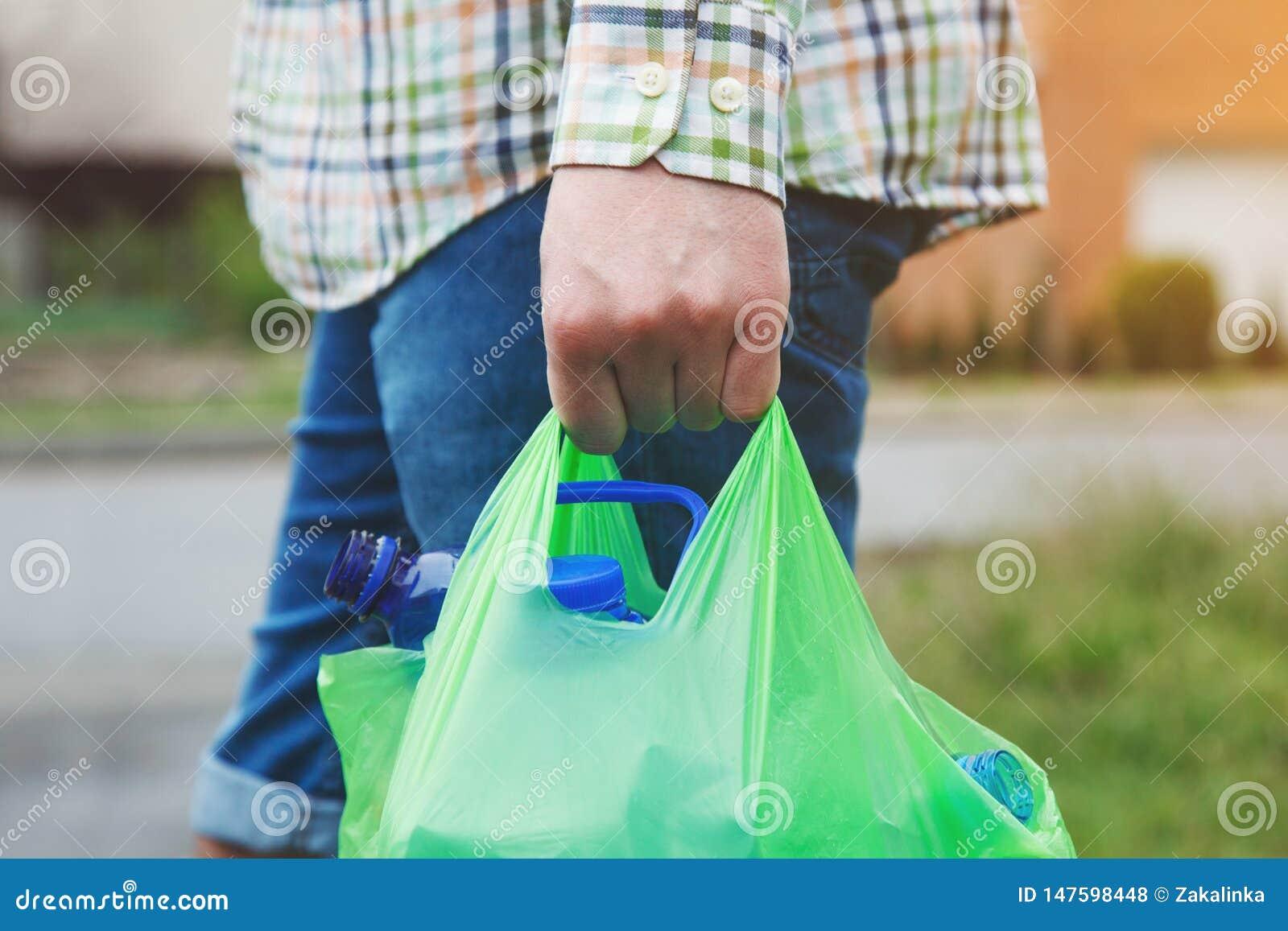 A mão do homem que leva o saco de plástico verde completamente de garrafas plásticas prontas para reciclar, espaço da cópia
