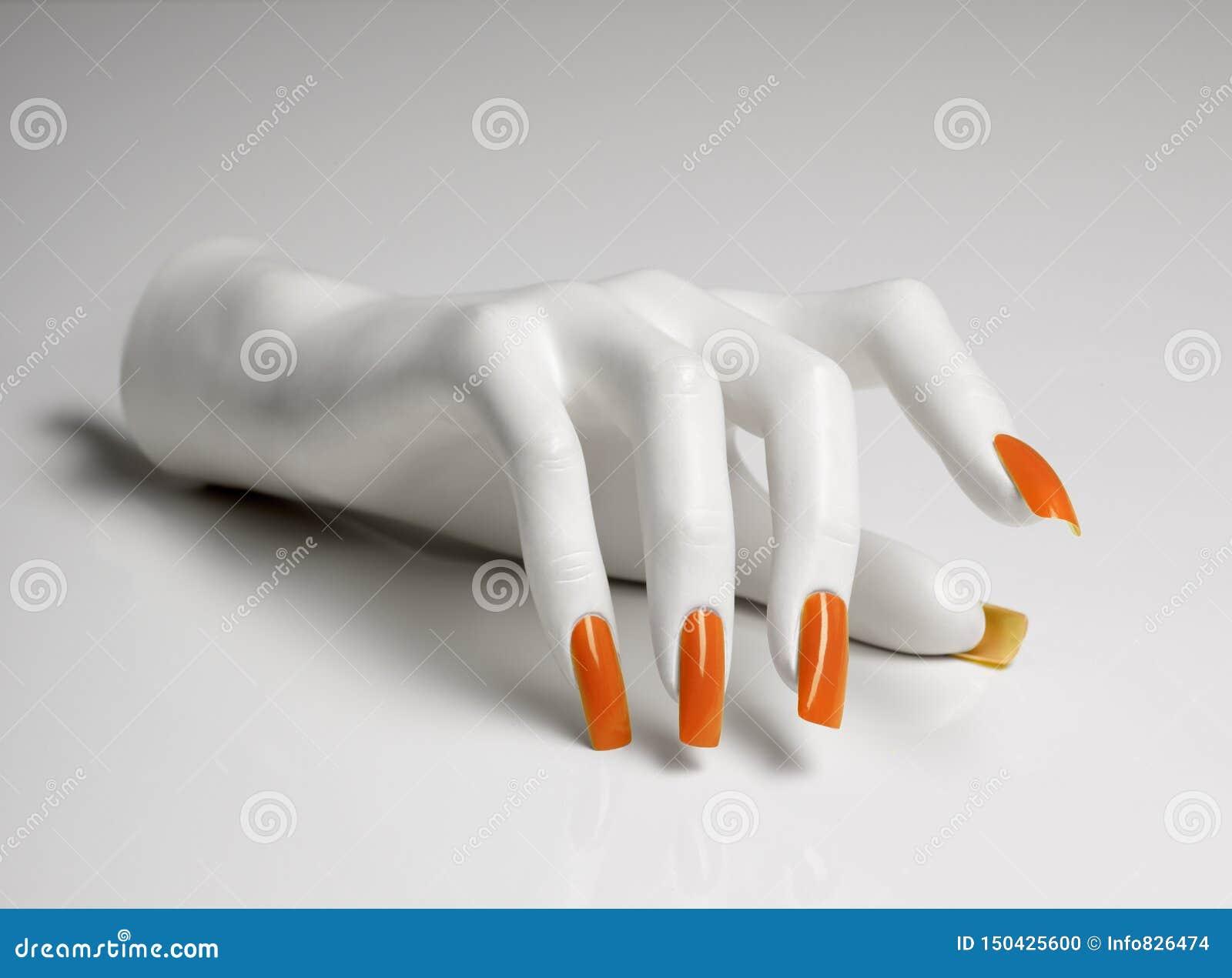 Mão do manequim com tratamento de mãos perfeito e verniz para as unhas alaranjado