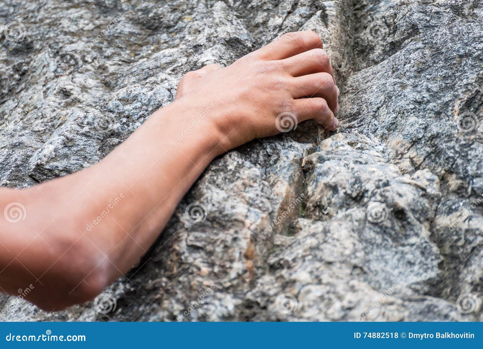 A mão do montanhista que guarda uma rocha